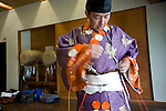 "Hirokazu Umezawa dresses himself in traditional attire prior to the ""yabusame-shinji"" horseback archery ritual on the final day of the Reitaisai grand festival at Tsurugaoka Hachimangu shrine in Kamakura, Japan on  14 Sept. 2012.  Photographer: Robert Gilhooly"
