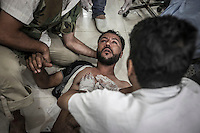 An opposition fighter lies on the floor of a hospital as he gets medical assistance after got injured during a combat with the Assad's army in Aleppo frontline.