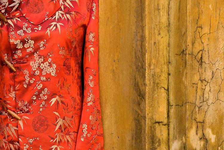 Silk Jacket - Red silk jacket against an ochre wall, Hoi An, Viet Nam
