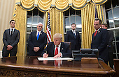 United States President Donald Trump prepares to sign a confirmation for Homeland Security Secretary James Kelly, in the Oval Office at the White House in Washington, D.C. on January 20, 2017.     <br /> Credit: Kevin Dietsch / Pool via CNP