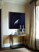 In one corner of the elegant dining room stands a gilt lacquered console table. The silk curtains are by Kravet.