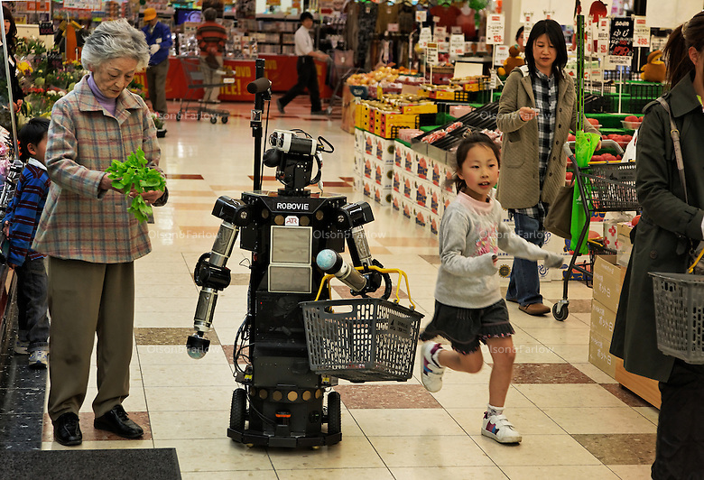 "All of these robotics folks developing robots for elderly talk about studies showing that more and more elderly are isolated and have no one to relate to... In 2009 it was 19 percent of the elderly population of Japan.  They have a word for it:  ""Kodokushi"" or ""lonely death."".The robotics folks at Keihanna Science City.http://www.kri-p.jp/english/history.html.http://web-japan.org/atlas/technology/tec07.html.cite these studies and are developing robots to help with shopping and other chores.  But mostly they are developing a companion to combat kodokushi.  The elderly Japanese person fills out a shopping list on their iPhone at their home and it is sent to the robot at the grocery store... when they walk into the store the robot recognizes them from the geolocation info in their iPhone and accompanies them on their shopping tasks, carrying the basket, reminding them of the items on their list and giving them information about the best freshest products that have come into the store on that day.  The eyes of the robot follow wherever the iPhone is to give the elderly the impression they have a friend.  The elderly woman shopping in this example is Nabeshima Akiko.  This grocery store is a functioning grocery store in the science city and is set up for demos of what this technology CAN do... but it is not functional yet.  They hope it will be in five years."
