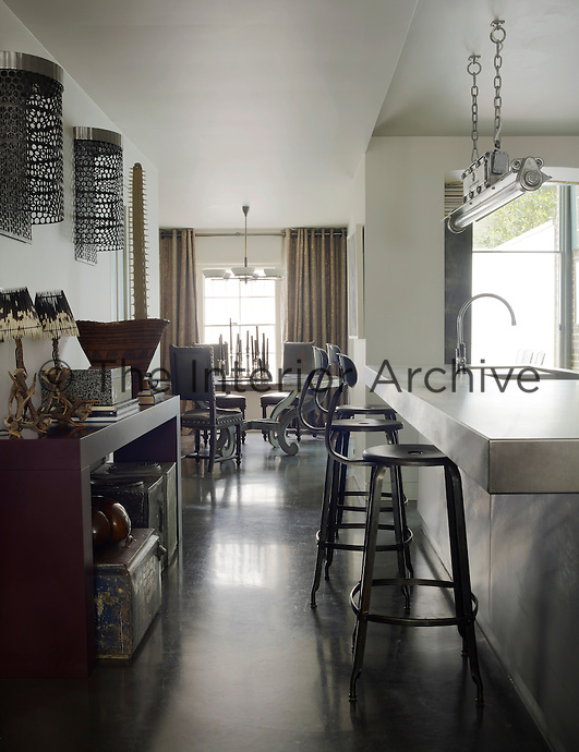 A light fixture from a French factory hangs above the stainless steel island in the kitchen and the barstools were found at a Paris flea market