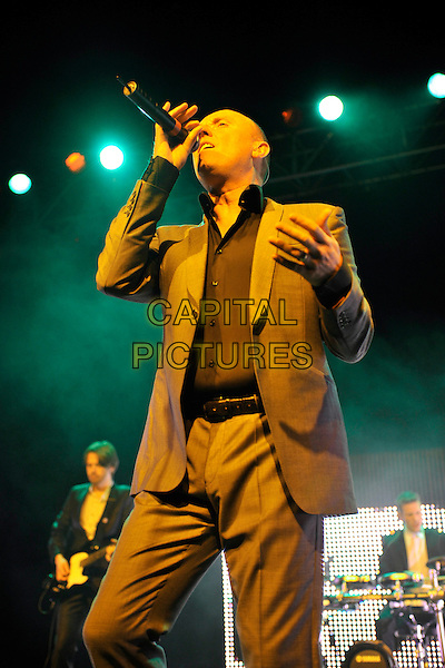 HEAVEN 17- Glenn Gregory.Heaven 17 performs on stage at HMV Forum, London, England. .November 28th, 2010.stage concert live gig performance music half length brown beige suit 3/4 singing .CAP/MAR.© Martin Harris/Capital Pictures.