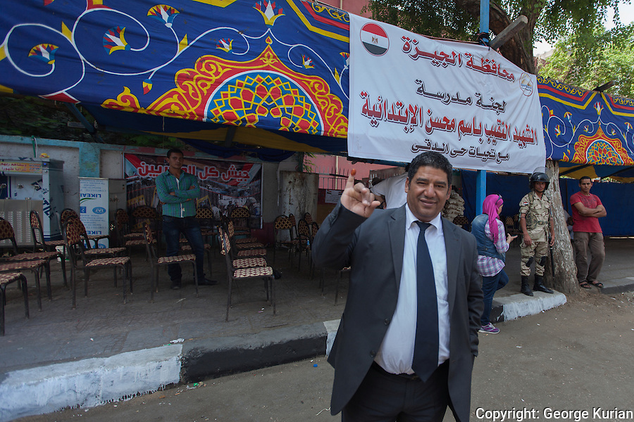 A voter displays the indelible ink on his little finger as he exits the polling station in Dokki, downtown Cairo.