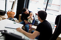 Mike Gutner (left), who handles operations at Mimo, his 10-month-old daughter Sadie Gutner as he speaks with Carson Darling, Mimo co-founder and co-CTO, the Mimo headquarters Boston, Massachusetts, USA, on Mon., April 28, 2014. Sadie, daughter of Mike Gutner, is wearing one of the company's onesies, made by Mimo, which has a variety of sensors on it. The onesie has a detachable frog-shaped communication device that transmits data from the onesie's sensors and sends the data to a smartphone app, which displays information about the baby's respiration, skin temperature, position, and activity level. The onesie is washable and the device is water-resistant.