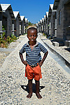 "Woodmay Pajeotle, 3, stands on a path amid houses in a model resettlement village constructed by the Lutheran World Federation in Gressier, Haiti. The settlement houses 150 families who were left homeless by the 2010 earthquake, and represents an intentional effort to ""build back better,"" creating a sustainable and democratic community. This boy and his mother are among the residents."