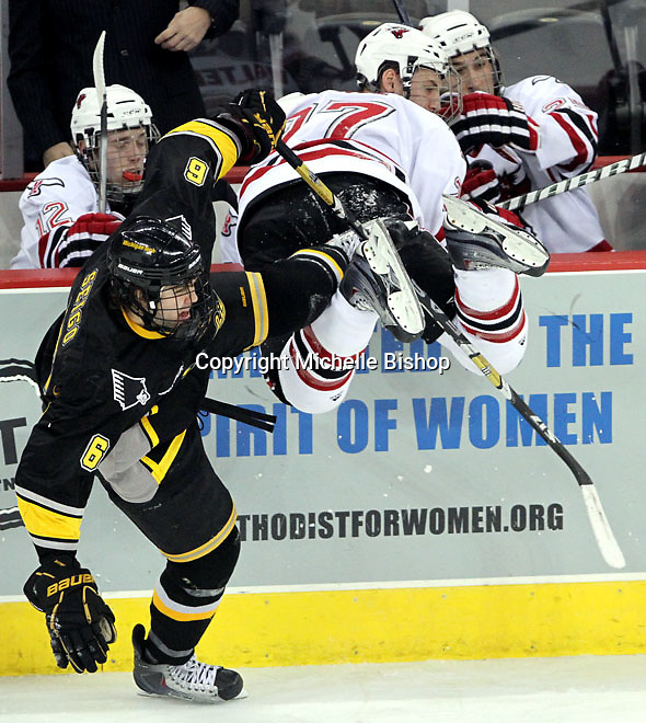 Michigan Tech's Steven Seigo sends UNO's Matt Ambroz into the Maverick bench during the third period. UNO defeated Michigan Tech 3-1 Friday night at Qwest Center Omaha. (Photo by Michelle Bishop)
