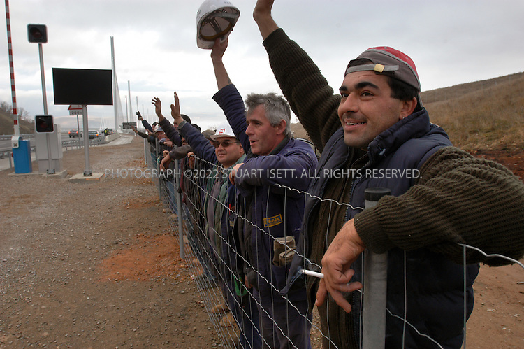 12/16/2004--Millau, France.Workers from the new Millau Bridge (behind) wave to drivers the first day the bridge opened. It is considered to be the world's tallest. One of the Millau bridge's pillars reaches more than eleven-hundred feet into the air, making it more than 50 feet taller than the Eiffel Tower. Designed by British architect, Norman Foster, the $523 million dollar bridge opens a new link between Paris and the Mediterranean....Photograph by Stuart Isett.©2004 Stuart Isett. All rights reserved