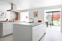A stylish white kitchen with a sink set in a central island unit. An open door area leads through to an extension area with sliding glass doors that give access to the garden.