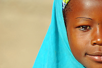 Niger, Niamey, Detail portrait of an african muslim girl wearing a turquoise tchador Few years ago photographers Anthony Asael and Stepahnie Rabemiafara dreamed a dream that seemed quite imposible: to visit every country of the World promoting arts and tolerance among children and, of course, taking photographs of them. With little money and resources but an impressing will, the duo got an astonishing goal. In four years they visited 300 schools in 192 countries where kids participating of the project created 18,000 pieces of artwork. <br />