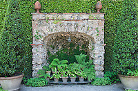 The lower grotto is filled with potted ferns arranged on a metal jardiniere