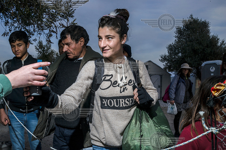 At a soup kitchen in the Kara Tepe camp, a young Yazidi girl accepts a hot drink from a volunteer.