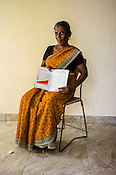 A Sri Lankan woman poses for a photo with the CHDR- Child Health Development Record Card (immunization/vaccination card) in the Ministry of Health office in Tharmapuram Village in Kilonochchi, Sri Lanka.  Photo: Sanjit Das/Panos