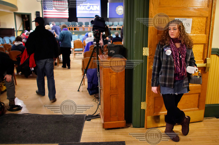 A campaign volunteer waits to greet arriving voters before the start of a town hall meeting with John McCain, Republican candidate for President, during the New Hampshire primary campaign. The Town Hall Meeting form of direct government was pioneered in New England and still governs most towns. Candidates now hold events called Town Hall Meetings hoping to draw on the direct democracy tradition.