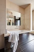 A modern bathroom with a washbasin set in a recessed unit with a mirorred front, which gives a sense of space to the room.