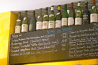 A blackboard chalkboard black chalk board with the wine list with wines served by the glass (Vins Au Verre), Savigny les Beaune, Chardonnay, Chassagne Montrachet, Pernand Vergelesses, Pacherenc de Vic Bilh Coteaux du Languedoc, Bourgogne, Chorey les Beaune, Gevrey Chambertin, with a selection of exclusive bottles on the shelf that has been drunk in the wine bar winebar at the restaurant Le Gourmandin in Beaune Cote d'Or Burgundy Bourgogne France Europe