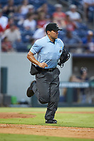 Home plate umpire Charlie Ramos hustles down the first base line during the International League game between the Scranton/Wilkes-Barre RailRiders and the Gwinnett Stripers at BB&T BallPark on August 16, 2019 in Lawrenceville, Georgia. The Stripers defeated the RailRiders 5-2. (Brian Westerholt/Four Seam Images)