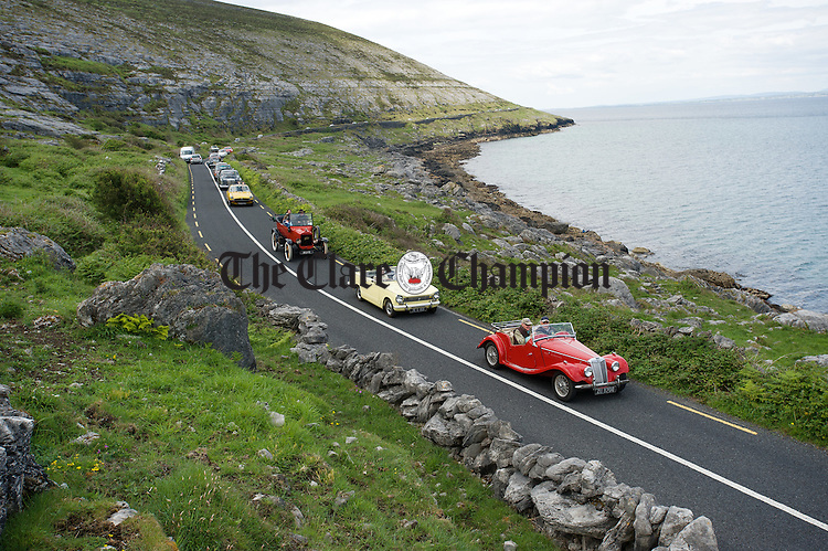 The line up of cars return to base along the coast road during a vintage run as part of Feile an Samhraidh at Ballyvaughan. Photograph  by John  Kelly.