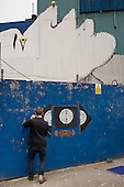 Daniel Burley, a student at Central St.Martins School of Art, assembles artwork on a hoarding in Shoreditch, London, a run-down commercial district  also known as Silicon Roundabout, which is undergoing gentrification as it becomes a centre for web-based companies and IT start-ups.