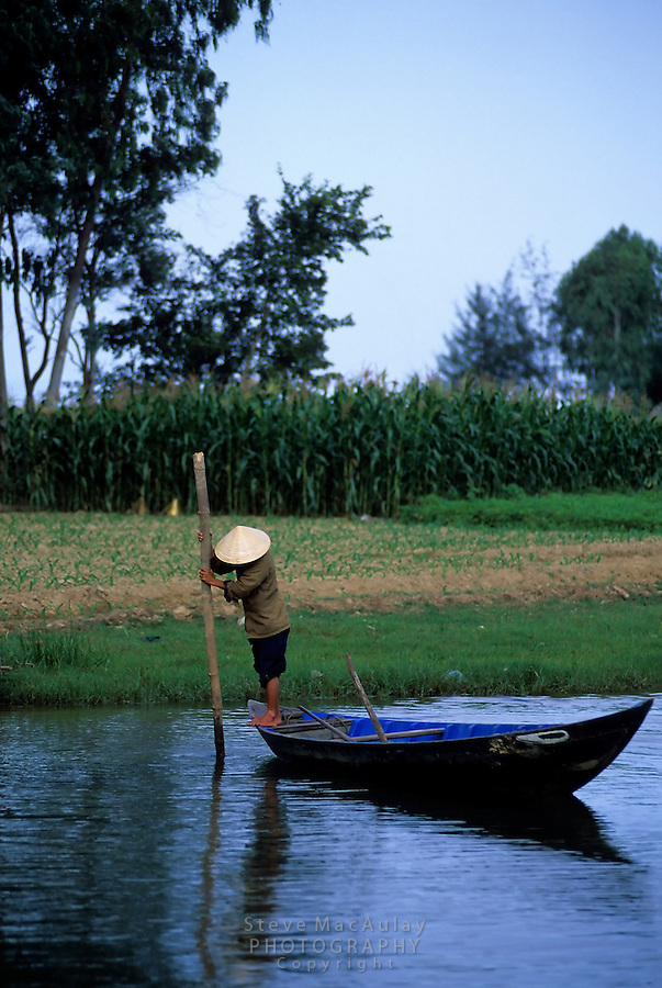 Boatman in traditional Vietnamese conical hat on Thu Bon River, Hoi An, Vietnam
