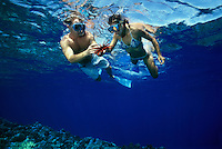This couple (MR) snorkeling in blue water over a Hawaiian reef are holding a slate pencil sea urchin, Heterocentrotus mammillatus.