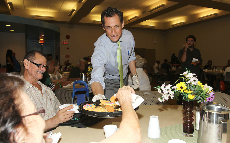 Anthony Weiner hands out cookies to seniors during his visit at the Cothoa Luncheon Club on Monday, August 12, 2013 in New York. (AP Photo/ Donald Traill)