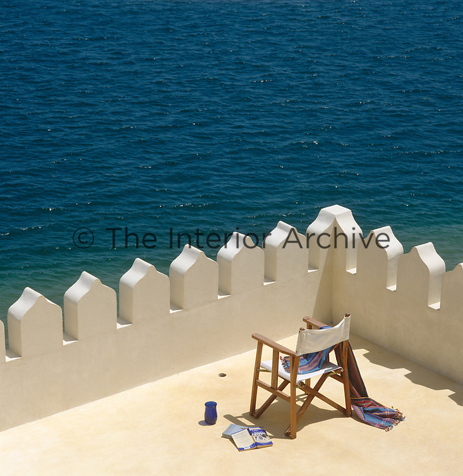 An abandoned chair on a castellated roof terrace with the azure waters of the Indian Ocean beyond