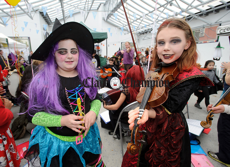 Isabel Enright and Mary Guy of Ennis Holy family school attending a public performance in the Market before the annual  Clare Champion Halloween Party. Photograph by John Kelly.