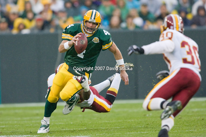 Quarterback Brett Favre #4 of the Green Bay Packers scrambles for yardage during an NFL football game against the Washington Redskins at Lambeau Field on October 14, 2007 in Green Bay, Wisconsin. The Packers beat the Redskins 17-14. (Photo by David Stluka)
