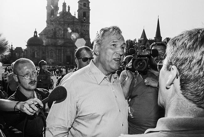 Mehrere hundert militante Neonazis aus Deutschland, Belgien, Frankreich, Daenemark, Schweden und Gross Britannien marschierten am Sonntag den 14. August 1993 zu einem sogenannten &quot;Rudolf Hess-Marsch&quot; im hessischen Fulda auf. Unter ihnen waren Mitglieder der Neonaziparteien Freiheitliche Deutsche Arbeiterpartei (FAP), Nationale Liste (NL) und NPD. Mit diesem Aufmarsch gedenken die Neonazis aus ganz Europa an den Hitler-Stellvetreter, der am 17. August 1987 im Kriegsverbrechergefaengnis in Berlin-Spandau mit 93 Jahren Suizid begangen hat.<br /> Im Bild: Der Nazi Friedhelm Busse gibt Interviews waehrend links der Neonazi Dieter Riefling versucht den Bodyguard zu machen.<br /> 14.8.1993, Fulda<br /> Copyright: Christian-Ditsch.de<br /> [Inhaltsveraendernde Manipulation des Fotos nur nach ausdruecklicher Genehmigung des Fotografen. Vereinbarungen ueber Abtretung von Persoenlichkeitsrechten/Model Release der abgebildeten Person/Personen liegen nicht vor. NO MODEL RELEASE! Nur fuer Redaktionelle Zwecke. Don't publish without copyright Christian-Ditsch.de, Veroeffentlichung nur mit Fotografennennung, sowie gegen Honorar, MwSt. und Beleg. Konto: I N G - D i B a, IBAN DE58500105175400192269, BIC INGDDEFFXXX, Kontakt: post@christian-ditsch.de<br /> Bei der Bearbeitung der Dateiinformationen darf die Urheberkennzeichnung in den EXIF- und  IPTC-Daten nicht entfernt werden, diese sind in digitalen Medien nach &sect;95c UrhG rechtlich geschuetzt. Der Urhebervermerk wird gemaess &sect;13 UrhG verlangt.]