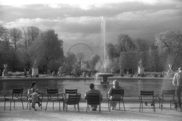 People relaxing around fountain in park, Paris, France infrared