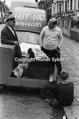 Young boy warming his hands from the heat from a hot Chestnut stall burner. The proprietor is talking to the Hot Dogs and Hamburgers van owner.  Stamford bridge Chelsea Football club while game is in progress. London England 1969