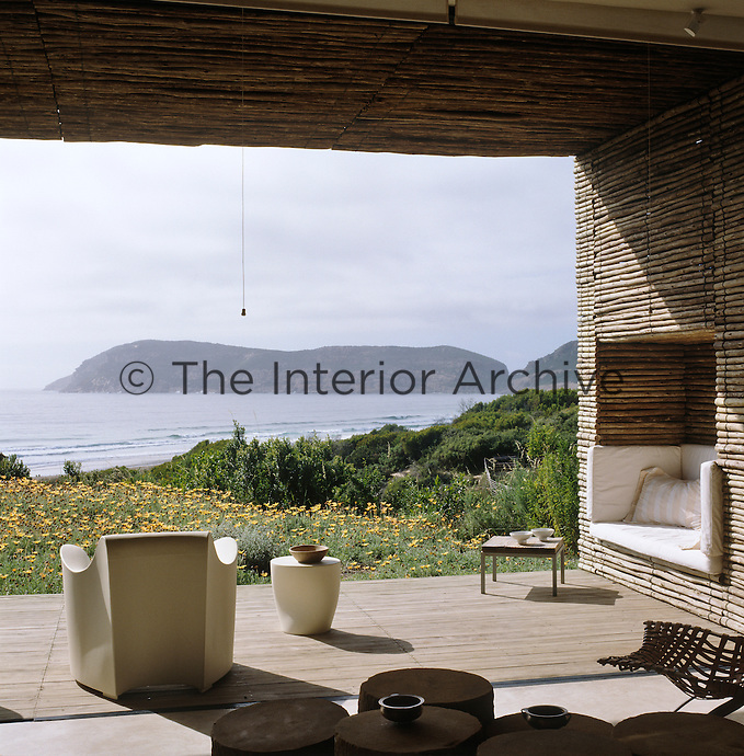 The view of Robberg Peninsula from the outdoor room with a recessed seating area and fibreglass chairs designed by Philippe Starck