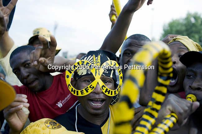 SOWETO, SOUTH AFRICA - DECEMBER 9: Soccer fans leave a game on December 9, 2006 in Soweto, Johannesburg, South Africa. They attended a derby between the archrivals Orlando Pirates and Kaizer Chiefs. The fans usually dress up. Soccer is the most popular sport in the black townships. (Photo by Per-Anders Pettersson/Getty Images).