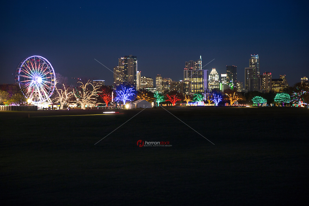 The Trail of Lights make up more than 100 trees covered in multi-color Christmas lights against the downtown Austin Skyline. This is a huge project hosted Parks and Recreation Department of the City of Austin.