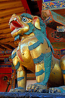 Ferocious guardian beast among the painted eaves, protecting the entrance to a shrine on the roof of the Jokhang Temple, Lhasa, Tibet, China.