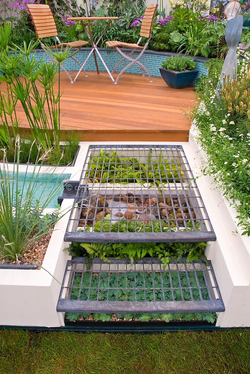 Creative use of small unused garden space: growing succulents and ferns under steps made of wire grate, leading to circular backyard deck