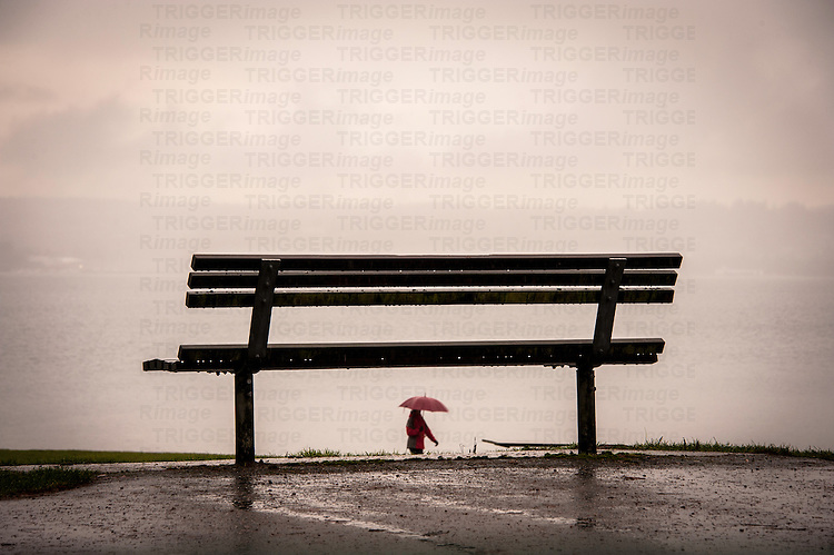 A woman in red with a red umbrella walking in the rain seen through a park bench on a wet day