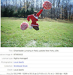 Cheerleader jumping in field, upstate New York,