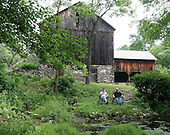 RJ Thornburg and Warren Muller enjoy a morning cup of coffee by the stream at their weekend home in Brodheadsville, Pa., on Monday June 12, 2006. The barn in the back will eventually become Mr. Muller's studio. Jane Therese for The New York Times