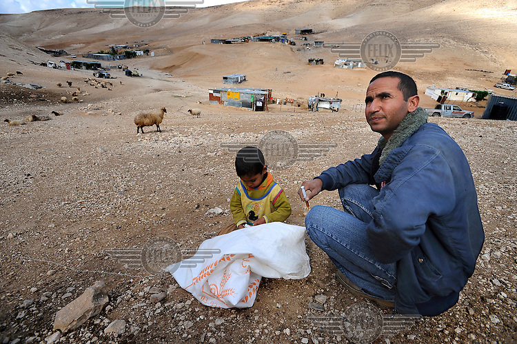 A man prepares a syringe to immunise his goats in an encampment of the Jahalin Bedouin tribe below the Palestinian town of al Azariyah in a part of the West Bank under Israeli control.