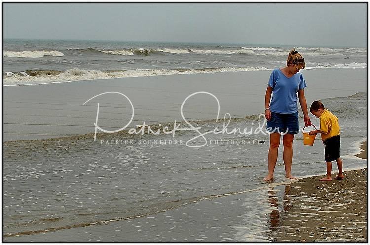 A mother and son collect rocks and shells while walking along a beach in the North Carolina Outer Banks. Photo is model released and can be used many places.
