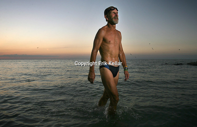 "Joe Bonness begins an evening swim in the Gulf of Mexico. ""The water is perfect now,"" he says. After a few minutes in the water, he comes upon a 3-foot dead shark. He grabs it by the tail, dangling it in the air while laughing. He says he often sees sand dollars and starfish, but never a shark that large so close to shore."