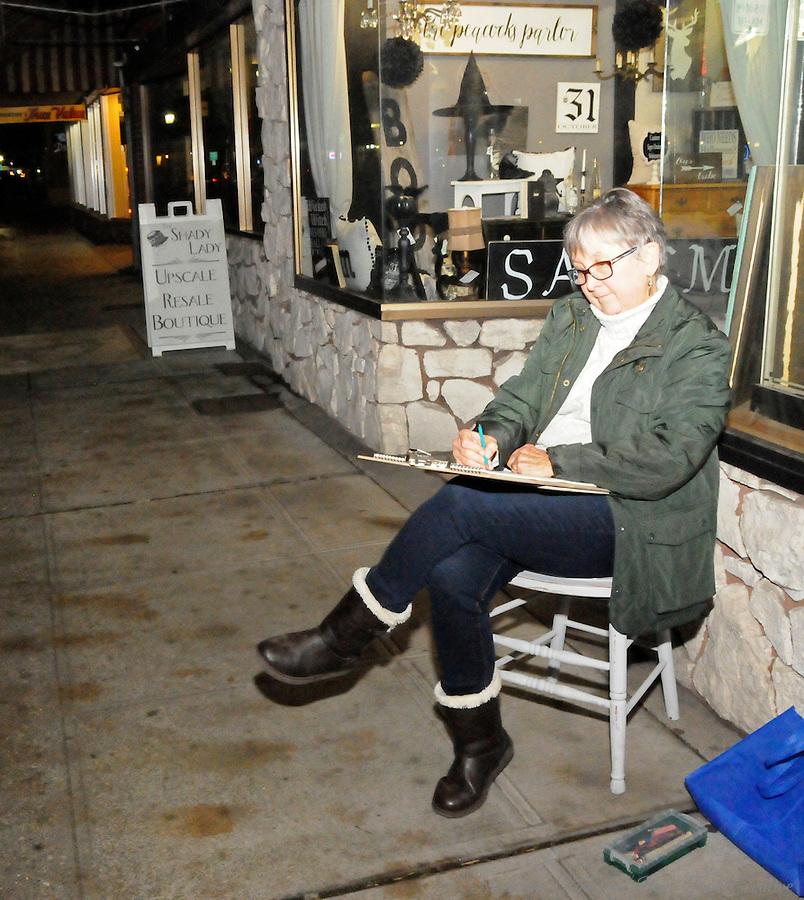Artist Jeanne Hamilton participates in the urban sketch crawl during Centralia, Washington's Third Thursday on October 20, 2016.