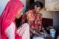 Nitu and Suki (in pink) (not their real names), cook together in their kitchen in Jhaju village, Bikaner, Rajasthan, India on 4th October 2012. Now 18, Nitu was married off at age 10 to a boy of around the same age, but only went to live with her in-laws when she was 12, after she had finished studying up to class 6. The three sisters, aged 10, 12, and 15 were married off on the same day by their maternal grandfather while their father was hospitalized. She was abused by her young husband and in-laws so her father took her back after hearing that her husband, who works in a brick kiln, was an alcoholic and was doing drugs and crime. She had only spent a few days at her husband's house at that time. Her father (now out of the hospital) has said that she will only be allowed to return to her husband's house if he changes his ways but so far, the negotiations are still underway. Her sister, Suki, now age 20, was married off at age 12 but only went to live with her husband when she was 14. Her husband died three years after she moved in, leaving her with a daughter, now 6, and a son, now 4. She has no parents-in-laws and thus returned to her parents house after being widowed because her brother-in-law, who had become the head of the family after his brother's death, had refused to allow Suki to inherit her deceased husband's fair share of agriculture land. Although Suki's father wants her to remarry, she refuses to, hoping instead to be able to support her family through embroidery and tailoring work. The family also makes hand-loom cotton to subsidize their collective household income. Photo by Suzanne Lee for PLAN UK