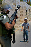 An Israeli border police officer stands ready to confront demonstrators in the West Bank village of An Nabi Salih near Ramallah on 09/07/2010.