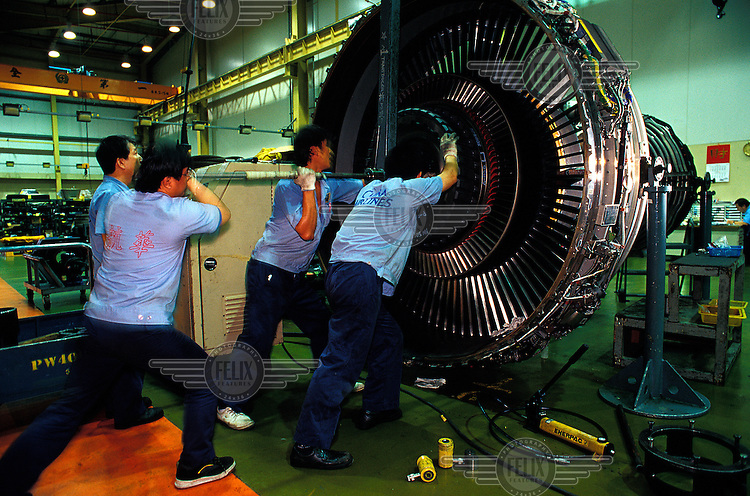 ©Chris Stowers/Panos Pictures..China Airlines maintainance technicians working on a jet engine in the Taiwan national carriers' maintainance hangar at Taipei's Chiang Kai-Shek Int'l Airport.