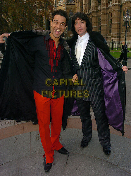 CHICO SLIMANI & LAWRENCE LLEWELYN BOWEN.Woman's Own Children of Courage Awards Departures, London..UK, United Kingdom.14th December 2005.Ref: CAN.full length with together opening black long leather coat fur trim collar pinstripe suit showing purple lining red trousers matching shirt funny funnies.www.capitalpictures.com.sales@capitalpictures.com.©Capital Pictures