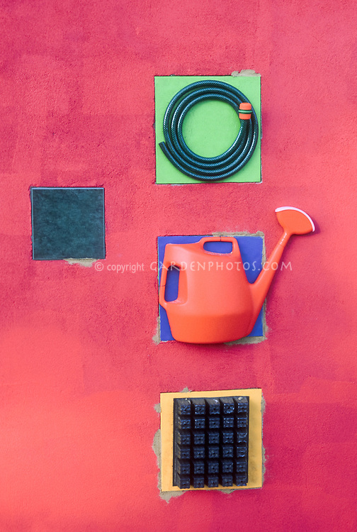 Whimsical garden wall ornaments inset, garden hose, seed plant flat, watering can, in red wall and primary colors tiles, decoration with sense of design, recycling upcycled garden tools, seed starting tray, plastic watering can. Bright colors, funny and charming re-uses